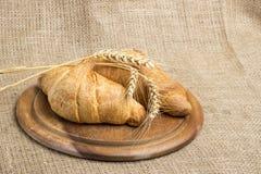 Latte della tazza dell'argilla, 2 croissant su un supporto di legno, spighette del grano, immagine stock libera da diritti