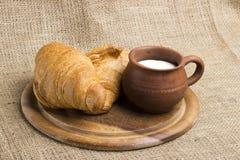 Latte della tazza dell'argilla, 2 croissant su un supporto di legno, spighette del grano, immagini stock