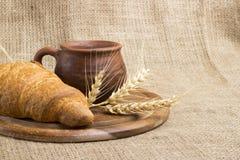 Latte della tazza dell'argilla, 2 croissant su un supporto di legno, spighette del grano, immagini stock libere da diritti
