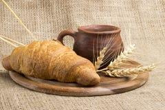 Latte della tazza dell'argilla, 2 croissant su un supporto di legno, spighette del grano, fotografia stock