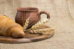 Latte della tazza dell'argilla, 2 croissant su un supporto di legno, spighette del grano, fotografie stock