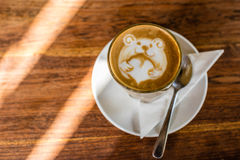 Latte della tazza di caffè con arte del latte di un orso che tiene un cuore di amore, sulla tavola di legno fotografia stock libera da diritti