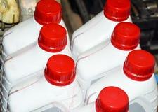 Latte di plastica bianche con i coperchi rossi Latte dell'olio della trasmissione Immagini Stock Libere da Diritti