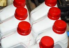 Latte di plastica bianche con i coperchi rossi Latte dell'olio della trasmissione Fotografia Stock