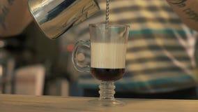 Latte di versamento di barista del caffè in tazza di vetro del caffè per la preparazione del latte in caffetteria archivi video