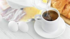 Latte di versamento dalla brocca nella tazza con il caffè nero di americano durante il primo piano della prima colazione archivi video