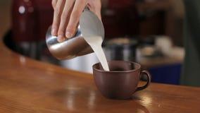 Latte di versamento del barista in tazza di cappuccino Fine in su archivi video