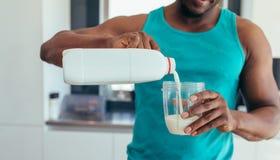 Latte di versamento dell'uomo in vetro per la prima colazione Fotografie Stock Libere da Diritti
