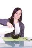 Latte di versamento della bella ragazza al suo cereale Immagini Stock Libere da Diritti