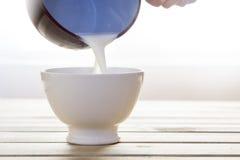 Latte di versamento della casseruola in ciotola da fare colazione Fotografia Stock