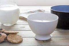Latte di versamento della casseruola in ciotola da fare colazione Fotografia Stock Libera da Diritti