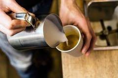 Latte di versamento di barista a caffè asportabile fotografia stock libera da diritti