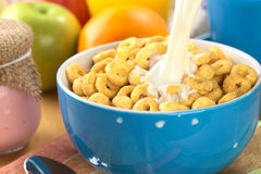 Latte di versamento sopra cereale aromatizzato miele Immagine Stock