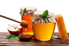 Latte di vetro in pieno di miele, delle mele e dei favi di legno Conta dell'archivio Fotografia Stock Libera da Diritti