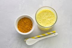 Latte dorato con curcuma in un vetro su un fondo di pietra grigio Fotografia Stock