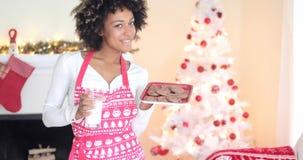 Latte e biscotti svegli della tenuta della giovane donna Fotografia Stock Libera da Diritti