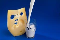 Latte e formaggio di versamento sopra priorità bassa blu. Immagine Stock Libera da Diritti