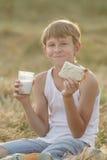Latte e pane adolescenti della tenuta del ragazzo dell'agricoltore Fotografia Stock Libera da Diritti
