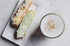 Latte eclairs przy kawiarnia stołem i kawa obrazy royalty free