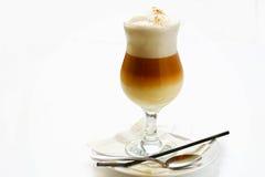 Latte en una taza de cristal en un platillo Foto de archivo libre de regalías
