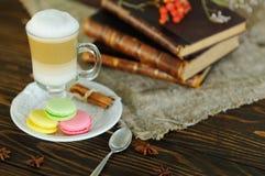 Latte et macarons sur un fond en bois sur le fond de vieux livres et de toile de jute Image libre de droits