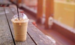 Latte för iskaffe i takeaway kopp på den wood tabellen Takeaway islat fotografering för bildbyråer