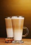Latte fragante de Ñoffee en la taza y el cinamomo de cristal Fotos de archivo libres de regalías