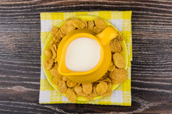 Latte giallo della brocca in piattino con il tovagliolo a quadretti dei fiocchi di mais Fotografia Stock Libera da Diritti