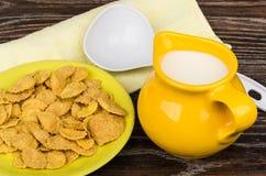 Latte giallo della brocca, piattino con l'asciugamano giallo dei fiocchi di mais Fotografie Stock