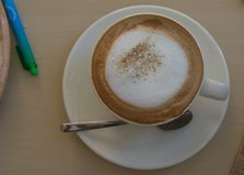 Latte in glass with foam and spoon top view royalty free stock photography