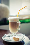 Latte in a glass glass. Delicious flavored coffee latte in tall glass goblet with a straw and biscuits is on the table Stock Photo