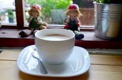 Latte-heiße Kaffee-und Kindergips-Puppe Stockfotografie