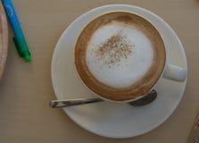 Latte i exponeringsglas med bästa sikt för skum och för sked arkivbild