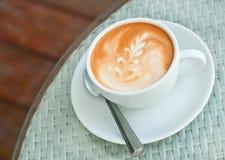 Latte konst på ett kaffe kuper Arkivfoto