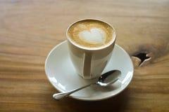 Latte Kunst auf einem cappucinno, auf hölzerner Tabelle Lizenzfreies Stockbild
