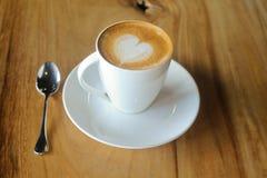Latte Kunst auf einem cappucinno, auf hölzerner Tabelle Stockfotos