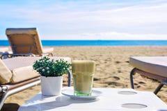 Latte à la plage Café glacé Frappuccino ou milk-shake dans un verre grand Fond Barcelone Espagne de vue de mer Image stock