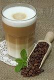 Latte Macchiato. In glass with coffee grain on brown background Stock Images