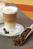Latte Macchiato. In glass with coffee grain on brown background Royalty Free Stock Photo