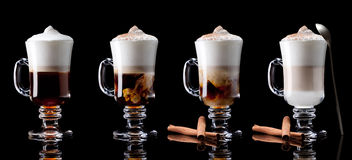 Latte macchiato. Cup of coffee latte macchiato on a black background Royalty Free Stock Photos