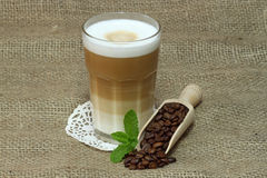 Latte Macchiato. In glass with coffee grain on brown background Royalty Free Stock Images