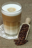 Latte Macchiato. In glass with coffee grain on brown background Stock Photos