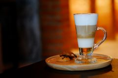Latte macchiato coffee Served with cookie in brown earth tone color background. And have some space for write wording royalty free stock photos