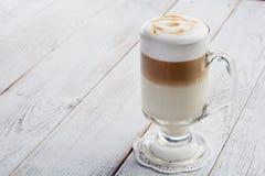 Latte macchiato coffee on white wooden background Stock Images