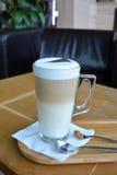 Latte Macchiato en la taza de cristal en una tabla de madera Foto de archivo libre de regalías