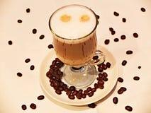Latte macchiato. Glass of latte macchiato with coffee beans Royalty Free Stock Photography