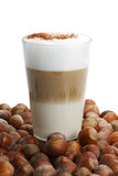 Latte macchiato between a lot of hazelnuts Royalty Free Stock Image