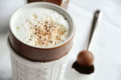 Latte macchiato with milk froth and a chocolate truffle Royalty Free Stock Images