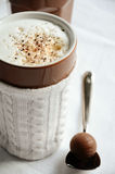 Latte macchiato with milk froth and a chocolate truffle Royalty Free Stock Photography