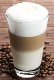 Latte macchiato mit Kaffeebohnen Lizenzfreie Stockfotografie